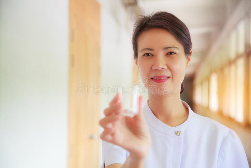 Enfermeira fêmea de sorriso que guarda o copo do comprimido em sua mão para pacientes Profissional, especialista, enfermeira, dou imagens de stock royalty free