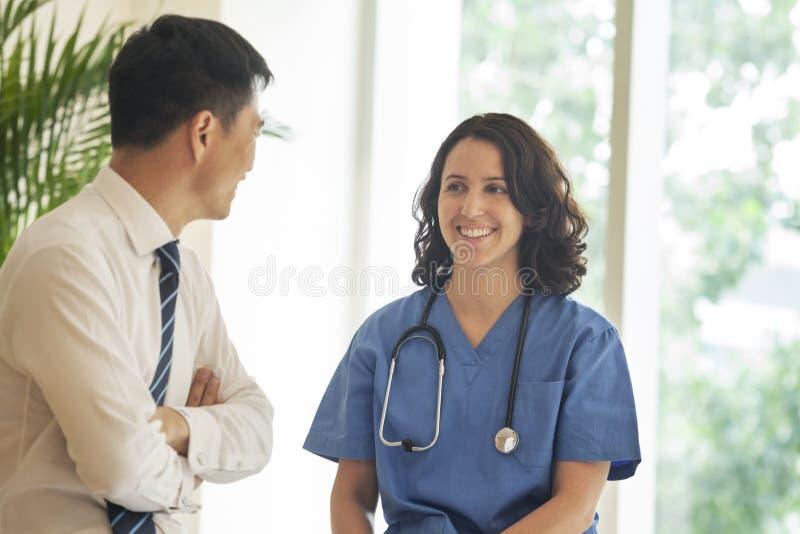 Enfermeira fêmea e paciente que falam e que sorriem no hospital fotografia de stock royalty free