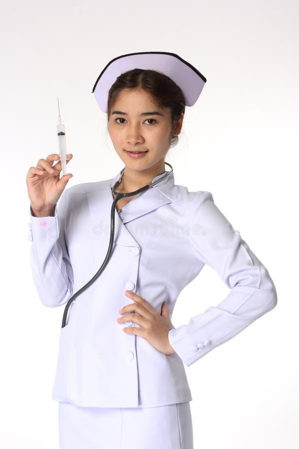 Enfermeira fêmea nova que guarda a seringa imagem de stock