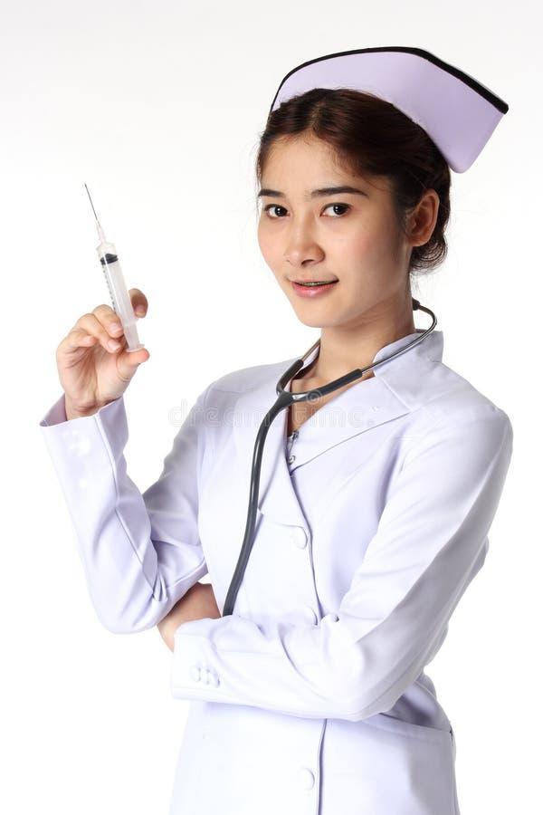 Enfermeira fêmea nova que guarda a seringa imagens de stock