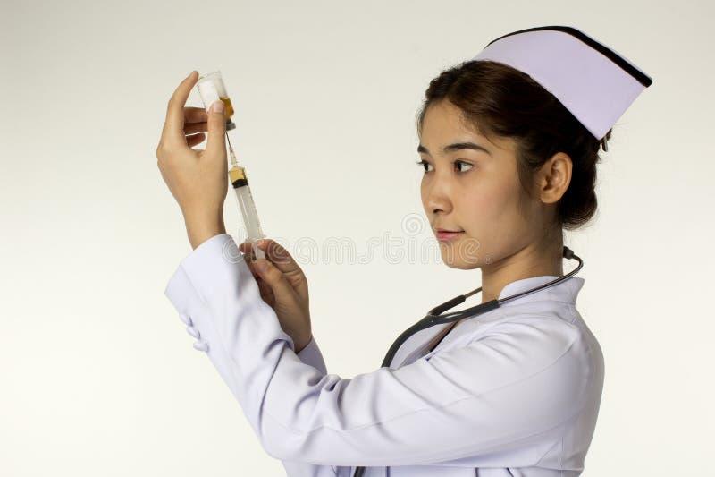 Enfermeira fêmea nova que guardara a seringa fotos de stock