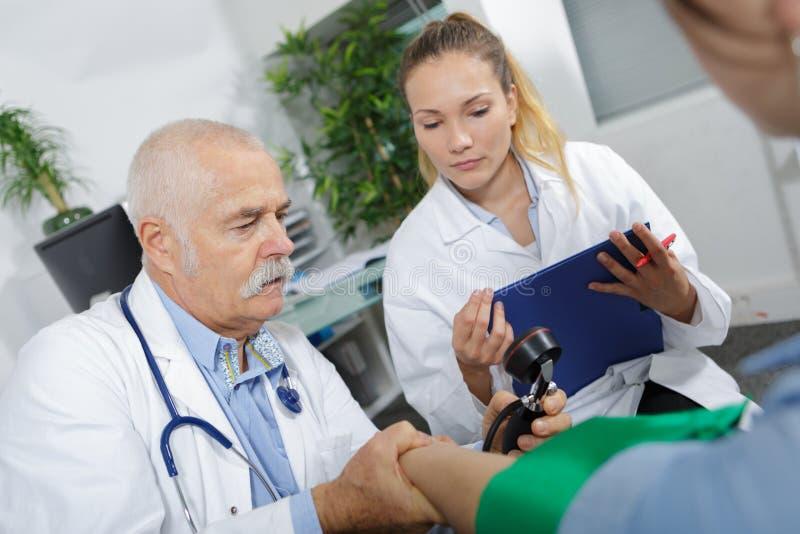Enfermeira fêmea que ajuda ao doutor superior durante a consulta fotos de stock royalty free