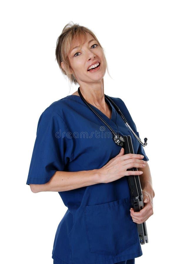 Enfermeira fêmea que carreg um portátil foto de stock royalty free