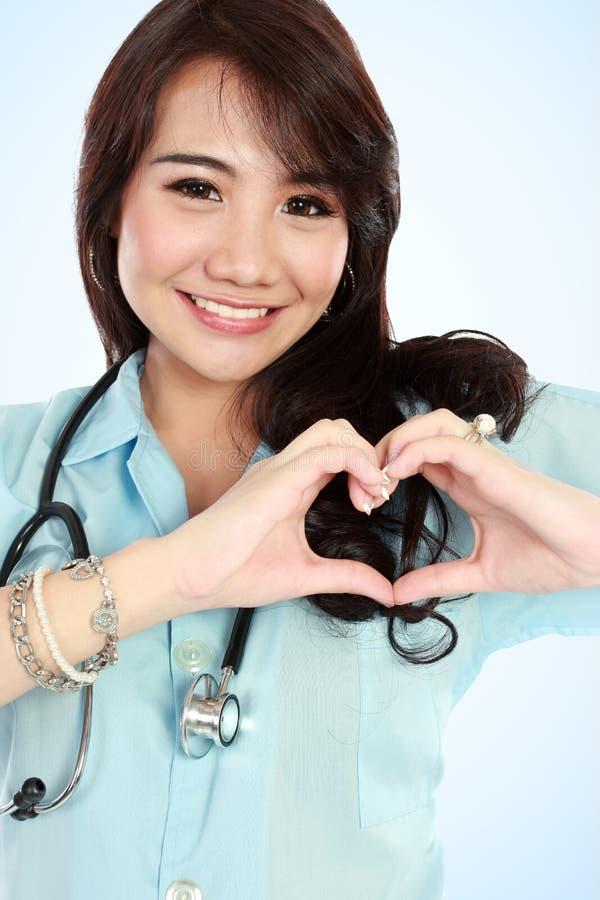 Enfermeira feliz dos jovens com mãos da fôrma do coração imagens de stock royalty free