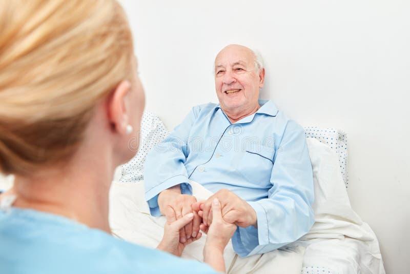 A enfermeira guarda as mãos de um paciente doente imagem de stock royalty free