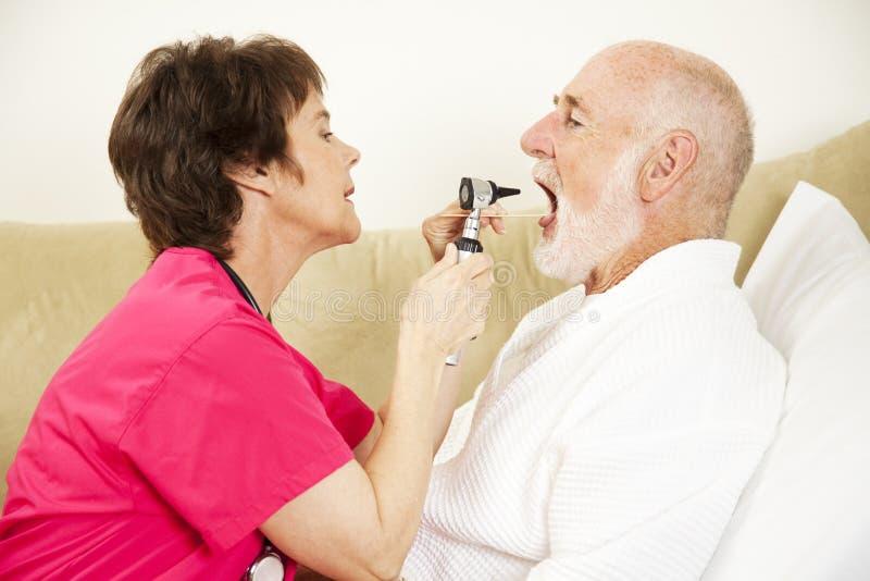 A enfermeira Home examina a garganta imagens de stock