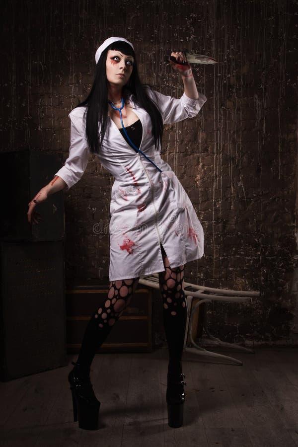 Enfermeira inoperante louca com a faca na mão fotografia de stock