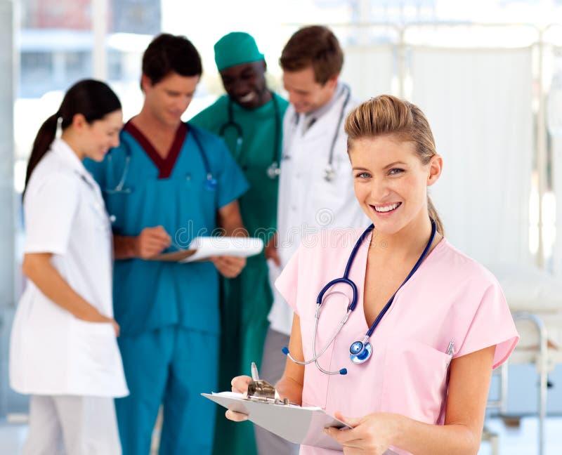Enfermeira loura com sua equipe no fundo fotografia de stock royalty free