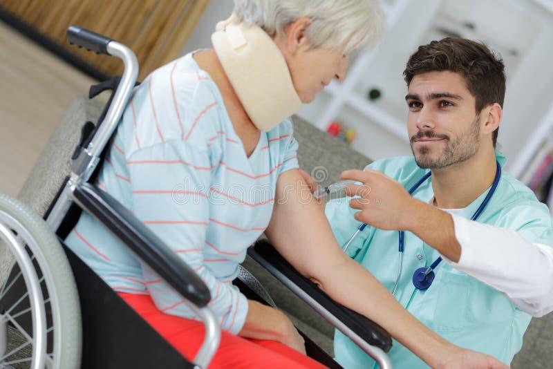 Enfermeira masculina que dá a injeção vacinal à mulher idosa foto de stock royalty free