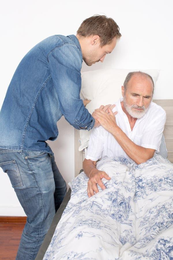 A enfermeira masculina toma de um homem mais idoso na cama fotografia de stock