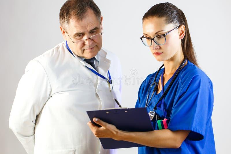 A enfermeira mostra ao doutor os resultados dos testes do paciente fotos de stock royalty free