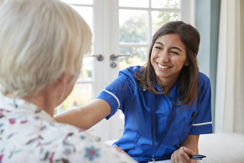Enfermeira nova do cuidado na visita home que consola a mulher superior foto de stock royalty free