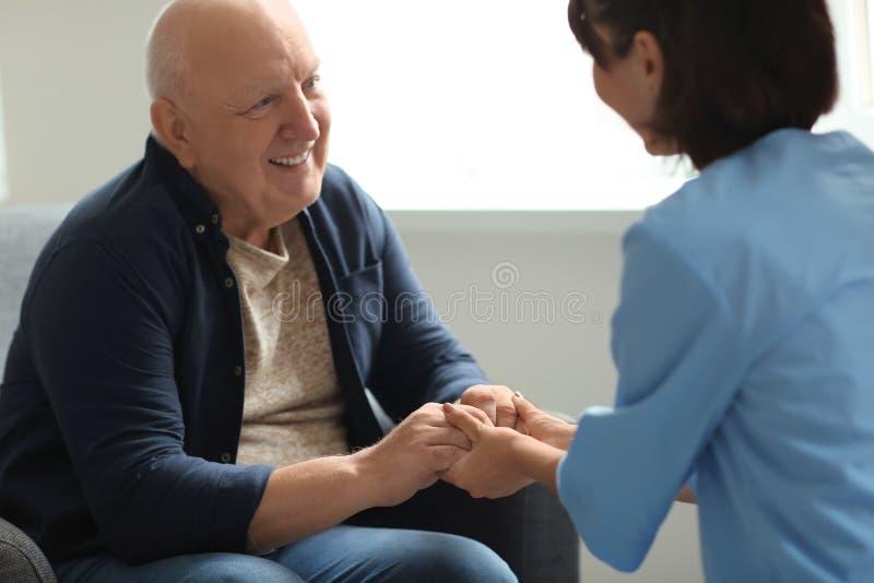 Enfermeira nova que visita a mulher idosa em casa foto de stock