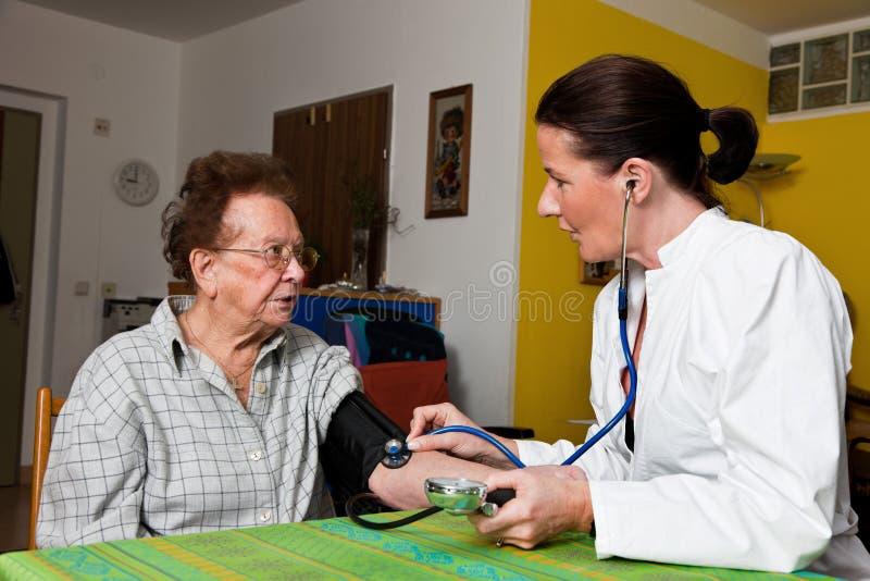 A enfermeira olha a mulher adulta em um lar de idosos fotos de stock royalty free