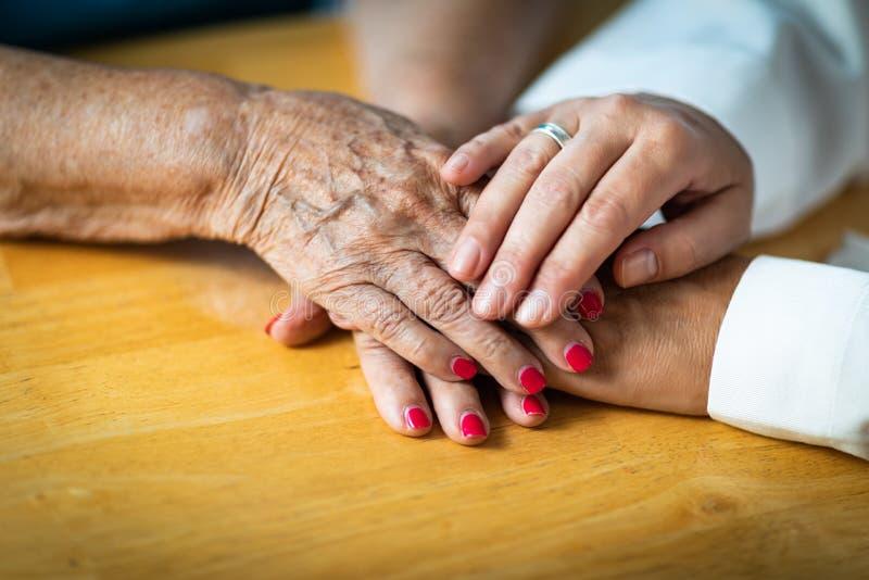 Enfermeira ou m?os da mulher adulta do doutor Hands Holding Senior imagem de stock royalty free