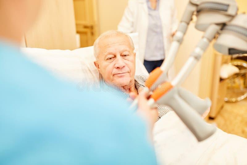 A enfermeira põe muletas sobre o paciente superior fotos de stock royalty free