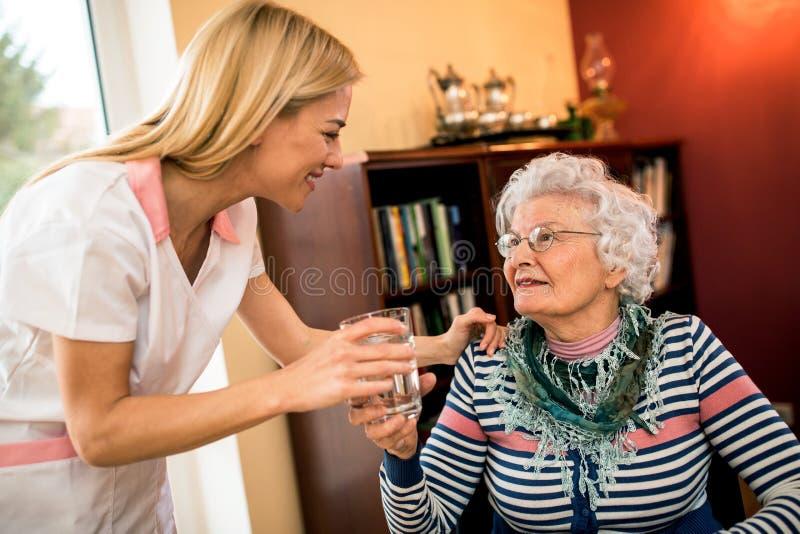 A enfermeira positiva de sorriso dos jovens traz a água ao paciente superior idoso imagem de stock