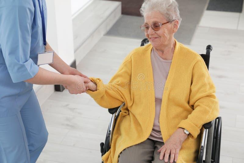 Enfermeira que ajuda à mulher superior na cadeira de rodas imagem de stock