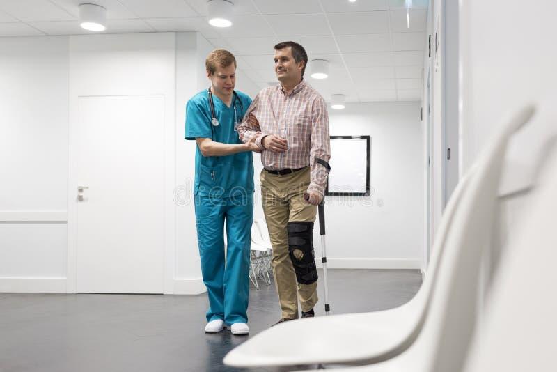 Enfermeira que ajuda ao paciente com pé ferido no passeio no corredor do hospital imagens de stock royalty free
