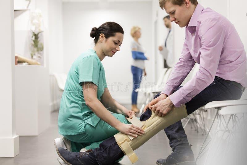 Enfermeira que ajuda ao paciente na cinta de joelho vestindo no hospital imagens de stock royalty free