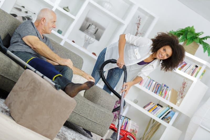 Enfermeira que ajuda o ancião deficiente a limpar a casa imagens de stock