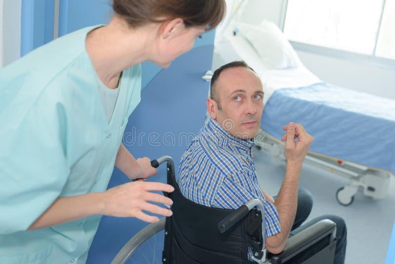 Enfermeira que ajuda o homem deficiente na cadeira de rodas imagens de stock royalty free