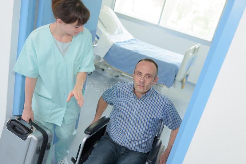 Enfermeira que ajuda o homem deficiente na cadeira de rodas fotos de stock