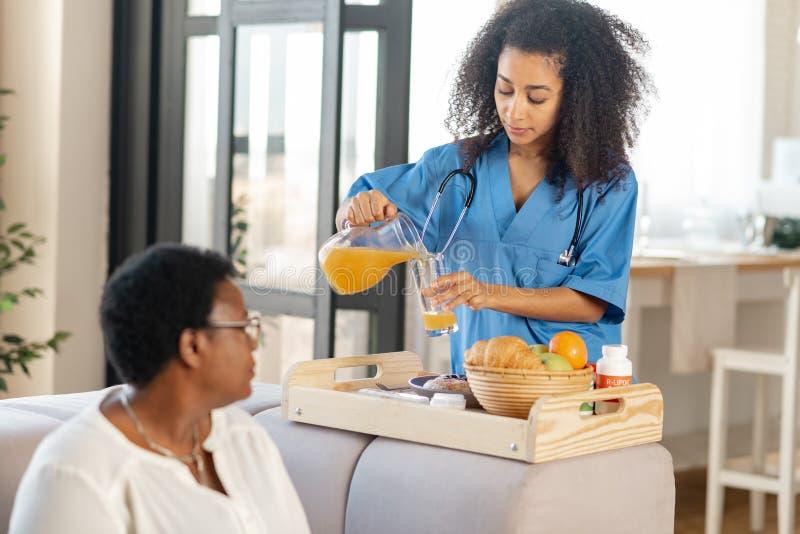 Enfermeira que derrama algum suco de laranja para a senhora que vive na casa de nutrição foto de stock