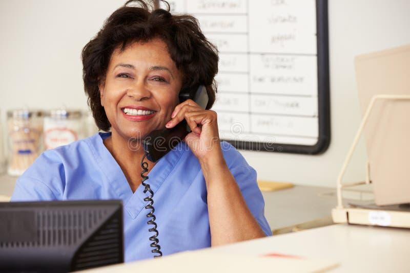 Enfermeira que faz o telefonema na estação das enfermeiras foto de stock