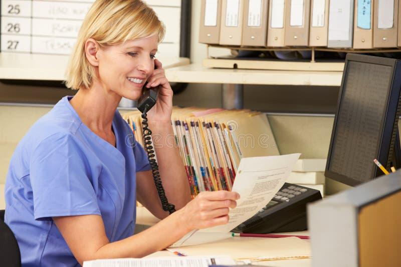 Enfermeira que faz o telefonema na estação das enfermeiras fotos de stock