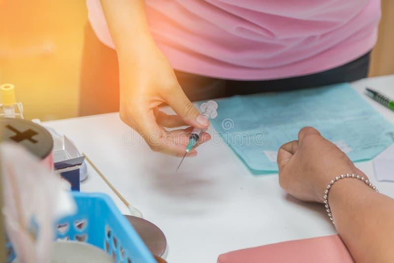 A enfermeira que mantém a seringa disponivel prepara a amostra de sangue do desenho do paciente do braço fotografia de stock royalty free