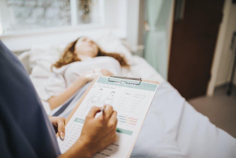 Enfermeira que nota abaixo da informação médica dos pacientes foto de stock royalty free