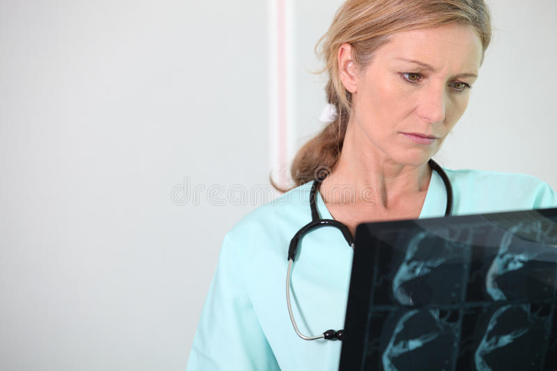 Enfermeira que olha o raio X imagens de stock royalty free
