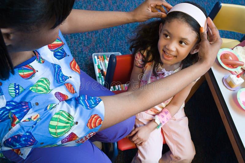 Enfermeira que põe a faixa sobre a menina fotos de stock