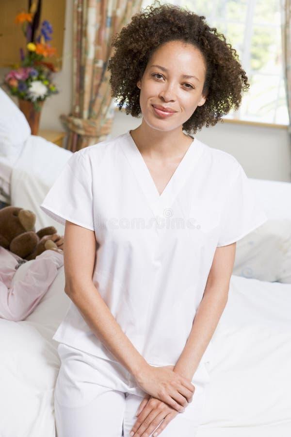 Enfermeira que senta-se na cama de hospital fotos de stock
