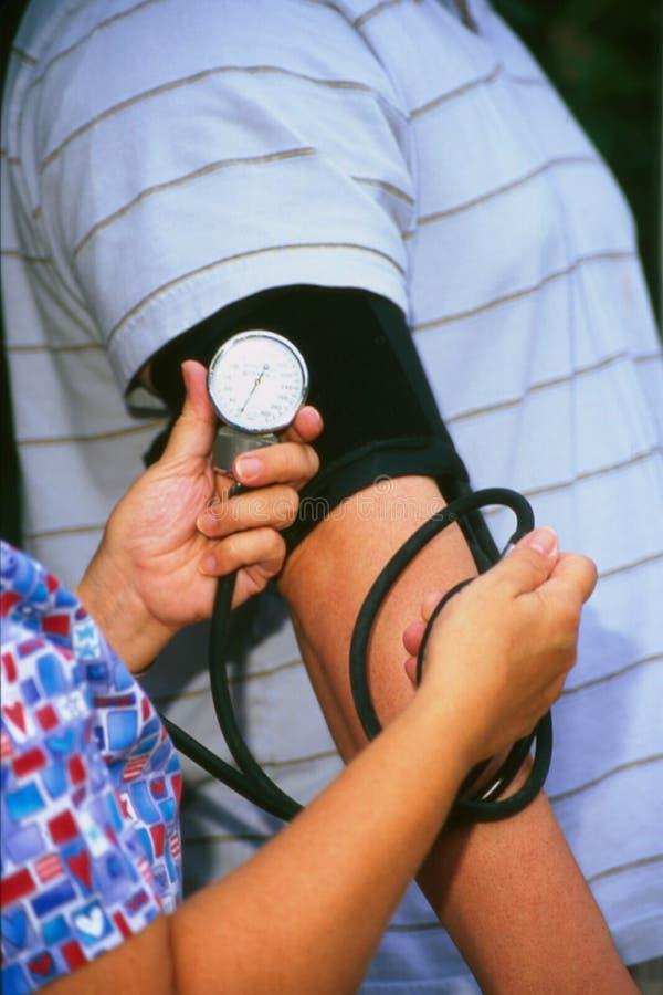Enfermeira que toma a pressão sanguínea imagens de stock royalty free