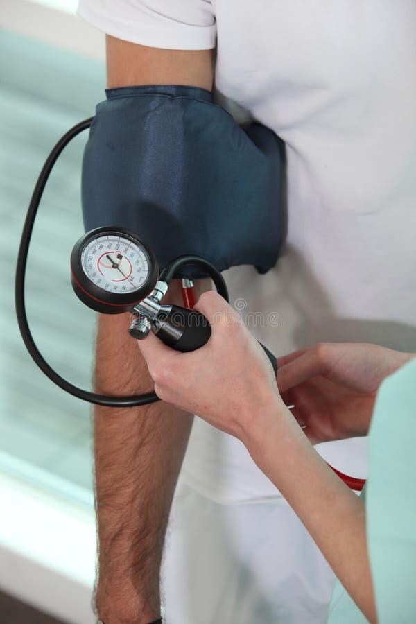 Enfermeira que toma a pressão sanguínea imagens de stock