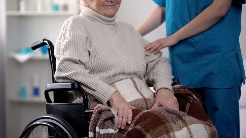 Enfermeira que toma sobre a mulher idosa na cadeira de rodas coberta pela cobertura, hospital foto de stock royalty free