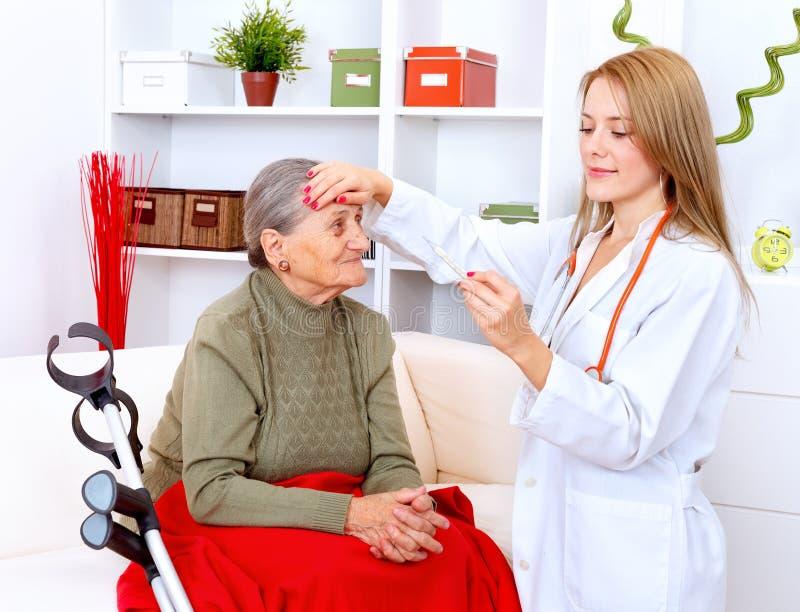 Enfermeira que toma a temperatura fotografia de stock