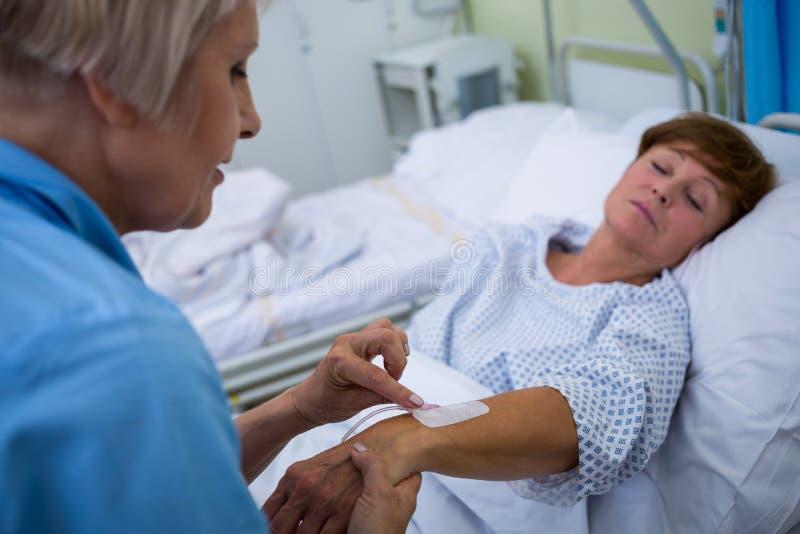 Enfermeira que une o gotejamento do iv na mão dos pacientes imagens de stock royalty free