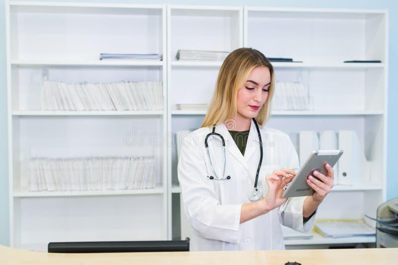 Enfermeira que usa a tabuleta digital na recepção do hospital moderno fotografia de stock