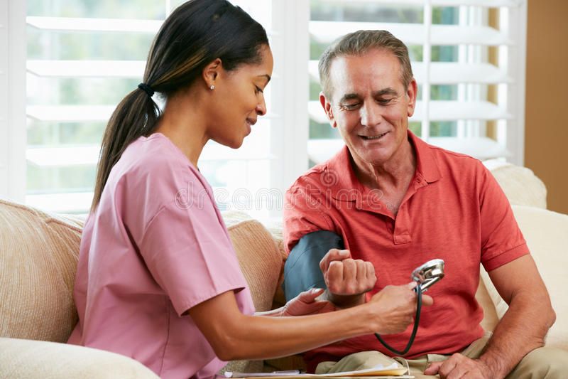Enfermeira que visita o paciente masculino superior em casa fotos de stock