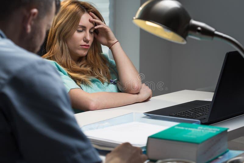 Enfermeira sobrecarregado que senta-se na mesa imagens de stock royalty free