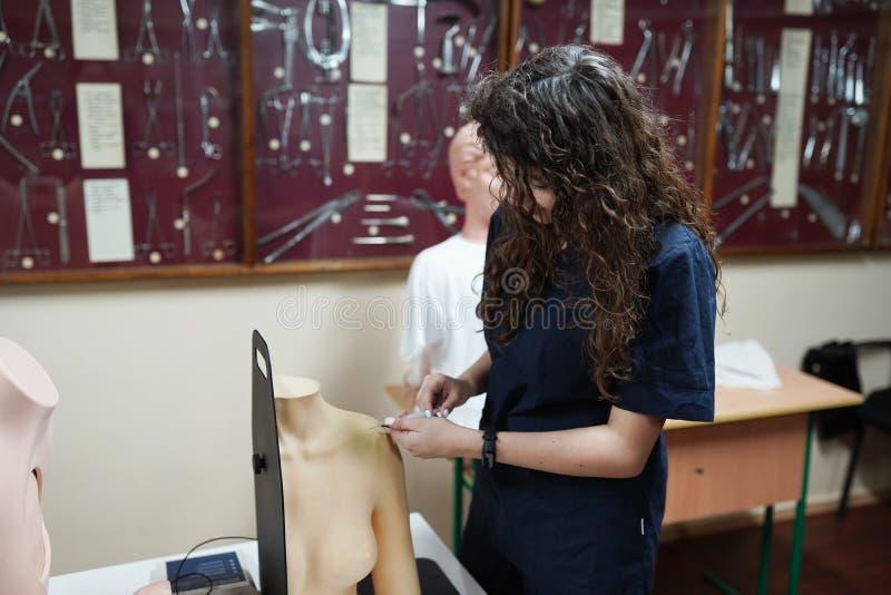Enfermeira usa luvas treinando injeção com modelo de braço para educação em hospital ou escola de enfermagem imagens de stock royalty free