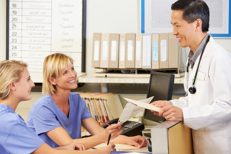 Enfermeiras do doutor Com dois que trabalham na estação das enfermeiras foto de stock royalty free