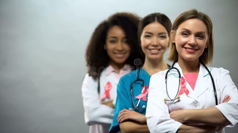 Enfermeiras multi-étnicos seguras com fitas cor-de-rosa, sinal internacional do câncer da mama fotos de stock royalty free