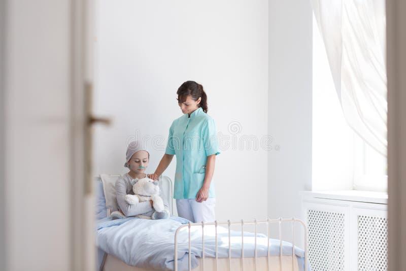 Enfermera útil que conforta al paciente adolescente enfermo con el cáncer en centro médico imágenes de archivo libres de regalías
