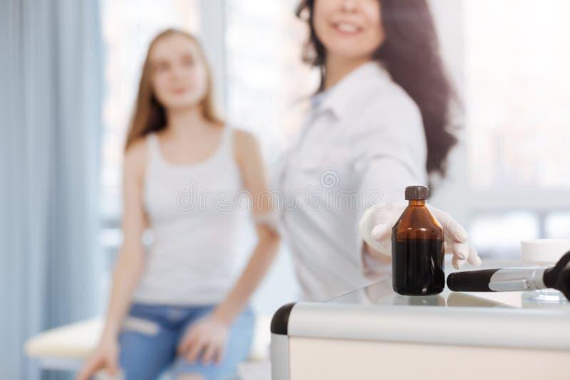 Enfermera útil que usa el yodo para la desinfección de piel en el hospital fotos de archivo