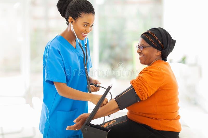 Enfermera africana que comprueba la presión arterial imágenes de archivo libres de regalías