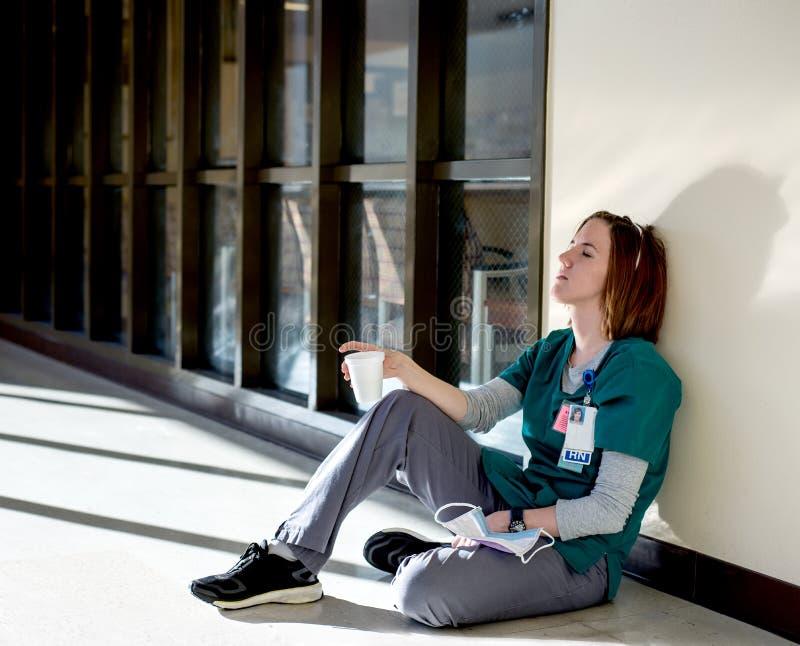 Enfermera agotada que se sienta en el piso imagen de archivo